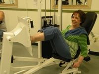 Woman sitting on leg press exercise machine looking into camera smiling