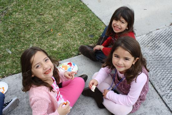 Little girls sitting on a sidewalk