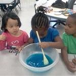 Children stirring a bowl with blue liquid