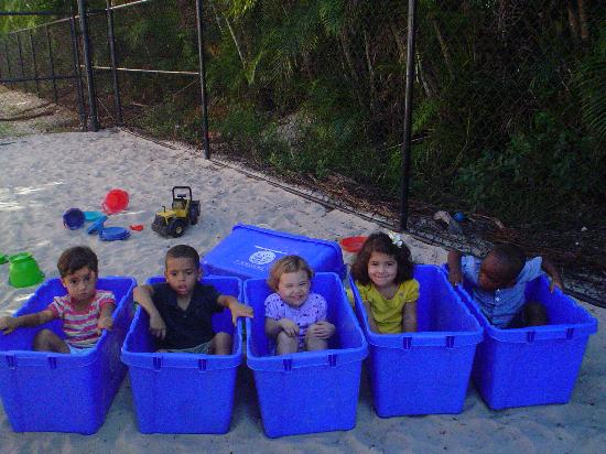 Children in plastic bins